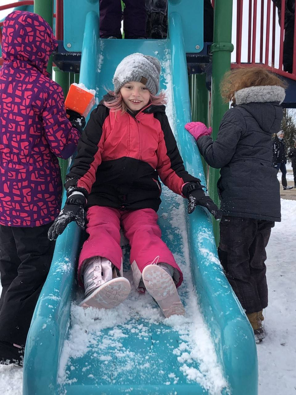 Student playing on slide at recess