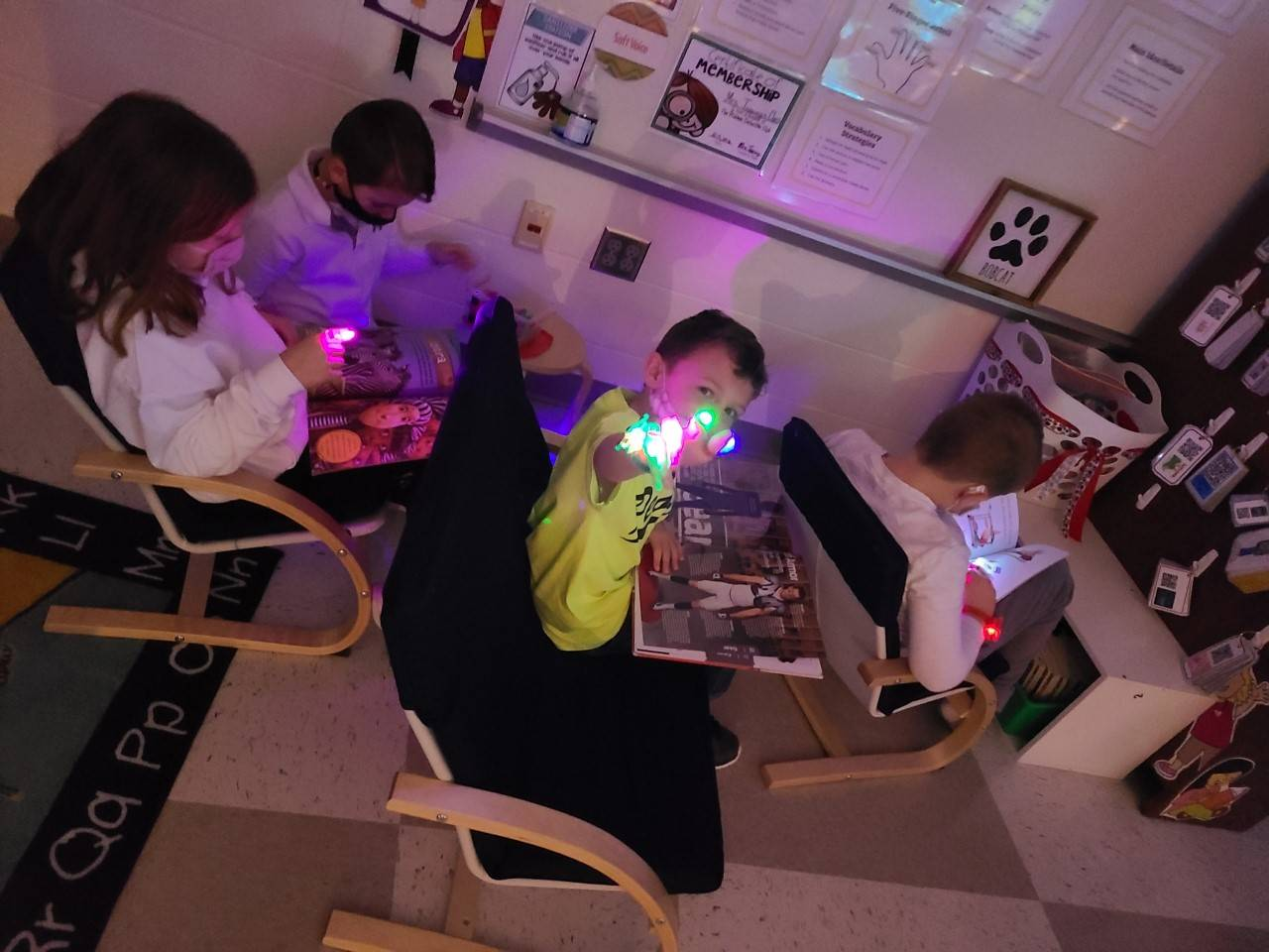 First grade students reading with finger lights