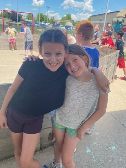 Two 4th grade girls outside with arms around one another