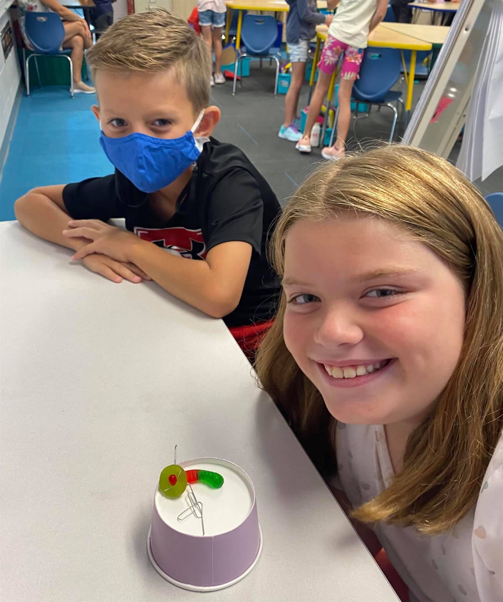 Two 3rd grade students working with gummy worm